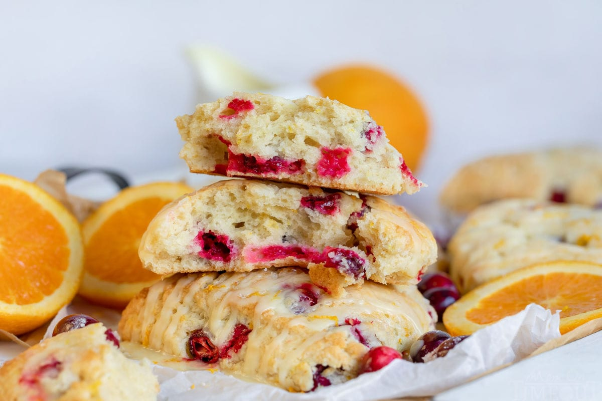cranberry orange scones split up and sitting on parchment paper with orange slices and cranberries scattered about