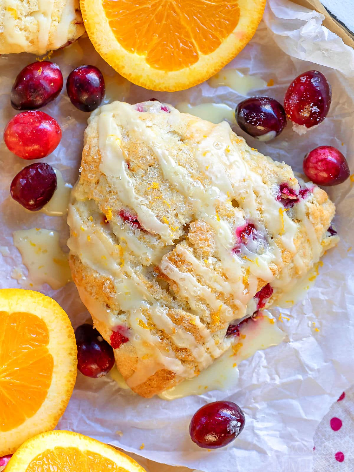 top down view of cranberry orange scone with cranberries scattered and orange slices on white parchment