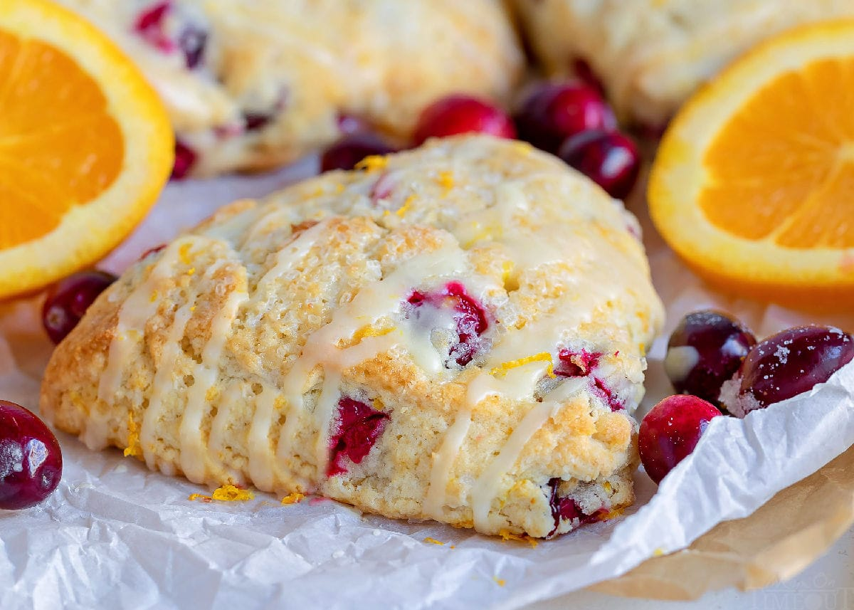cranberry orange scones with orange glaze on top of white parchment with orange slices in background
