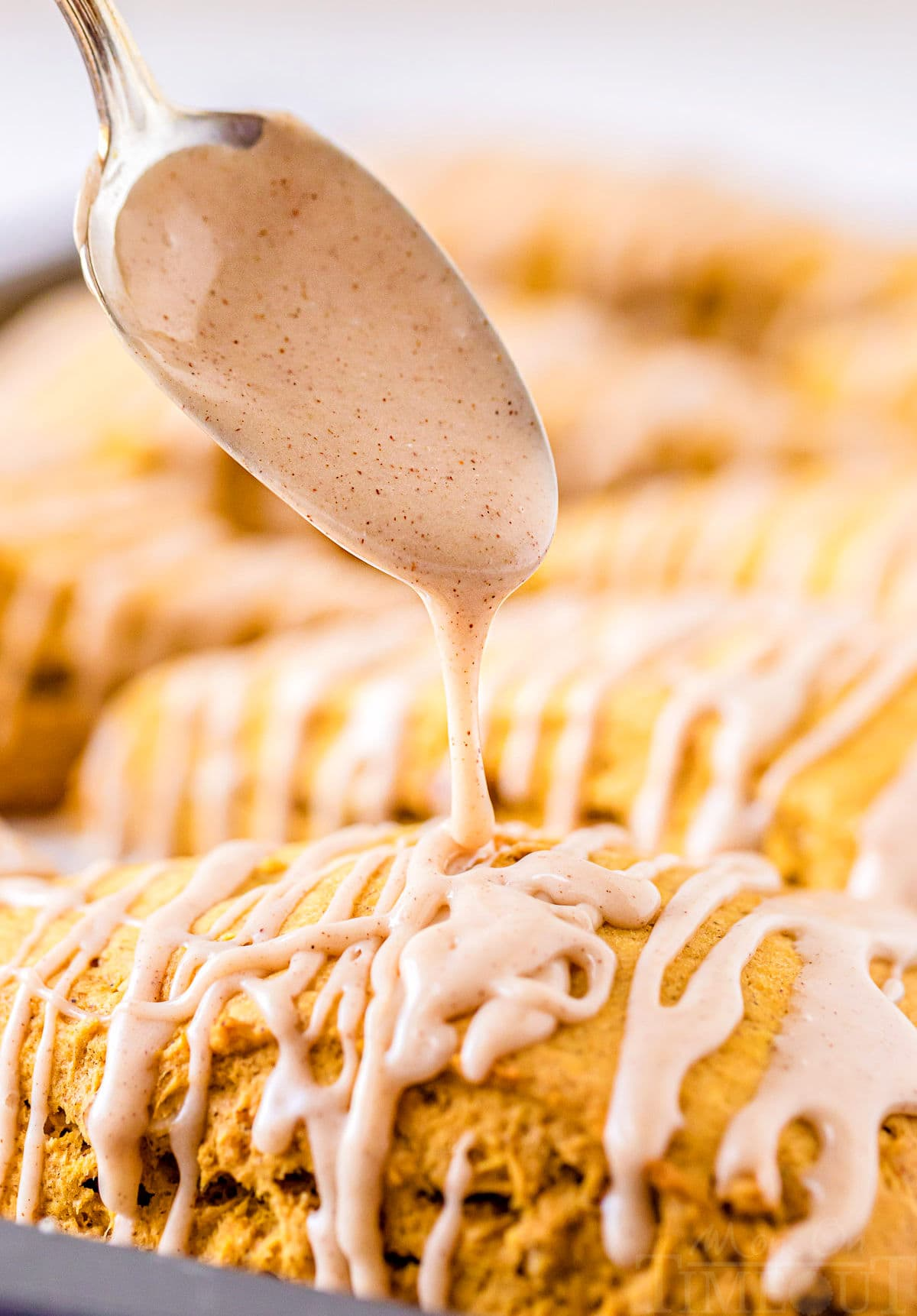 maple cinnamon glaze being drizzled on scones