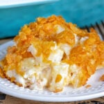 cheesy potatoes on a white plate with casserole dish in background