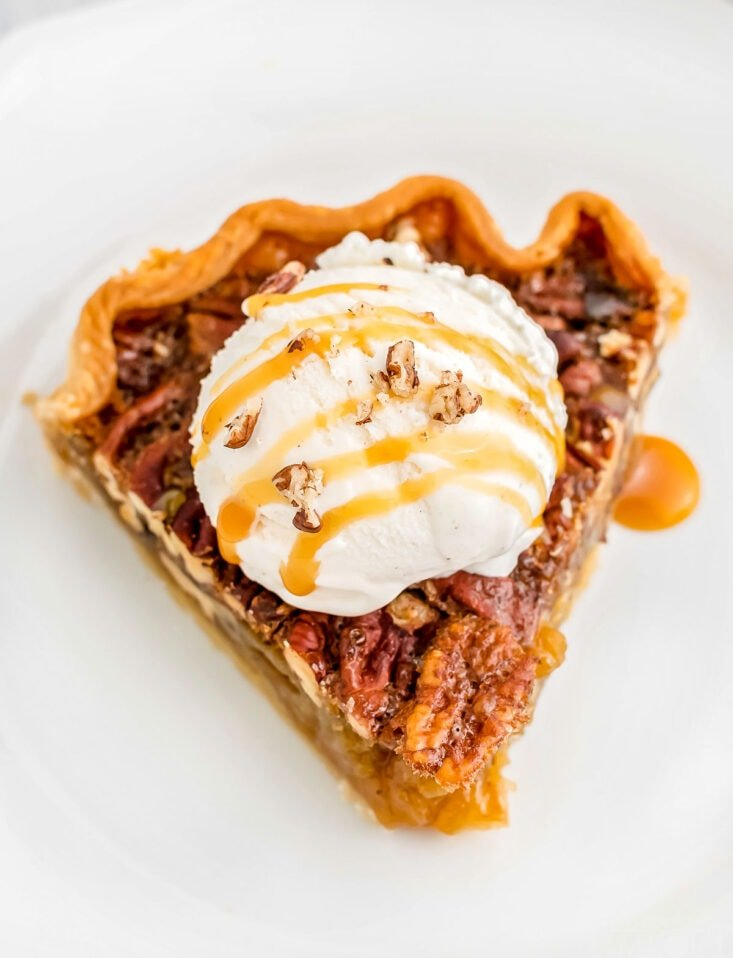 maple pecan pie recipe on white plate topped with vanilla ice cream and caramel drizzle