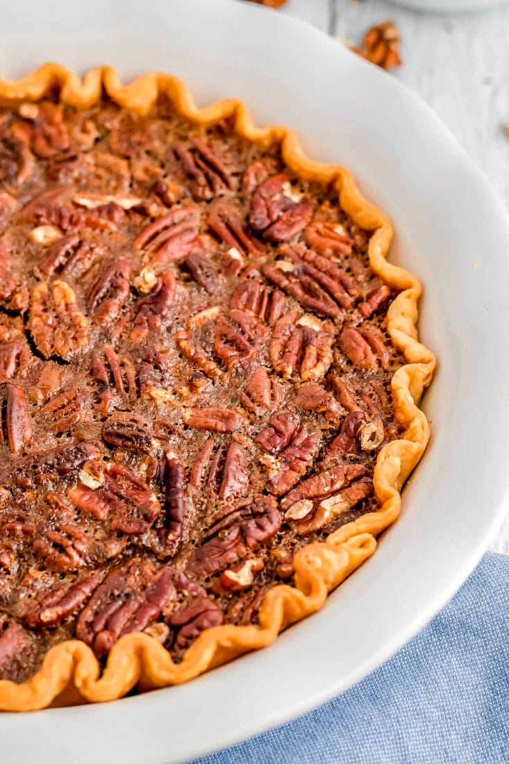 whole pecan pie in pie plate with light blue napkin beneath