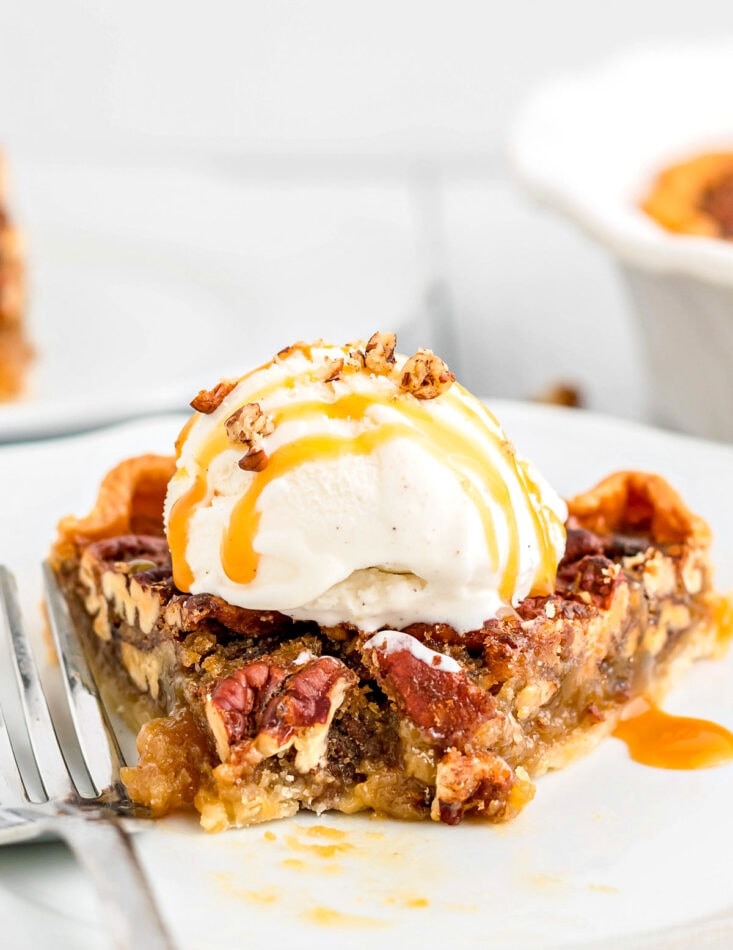 pecan pie slice on plate with bite taken topped with ice cream and caramel sauce