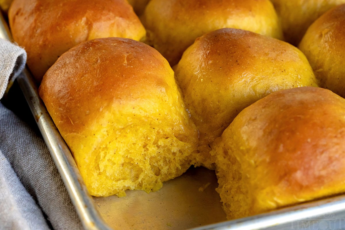 pumpkin dinner rolls baked in sheet pan with one removed