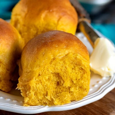 three pumpkin dinner rolls on a white plate with butter on the side
