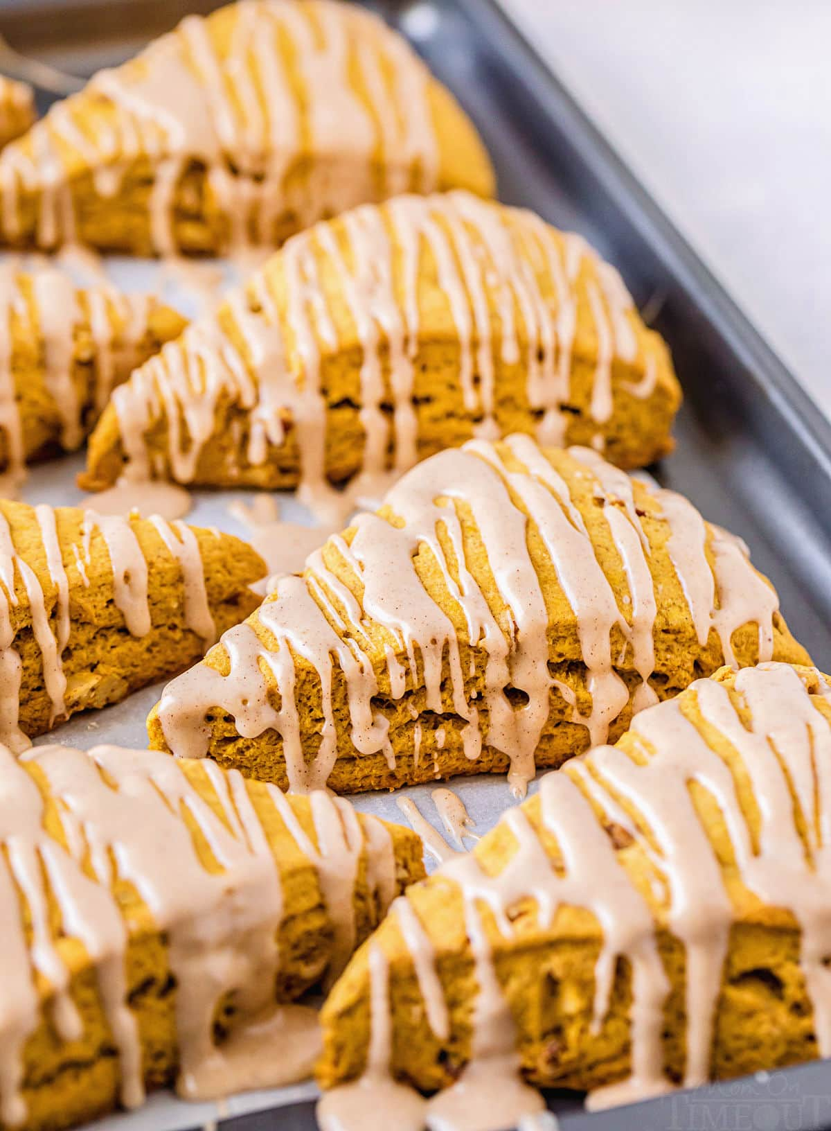 pumpkin scones on baking sheet with glaze drizzled on