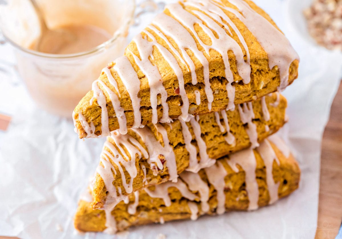 pumpkin scones stacked top down view with a maple glaze drizzled on top