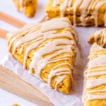 pumpkin scones sitting on white parchment on a wood cutting board with a maple cinnamon glaze