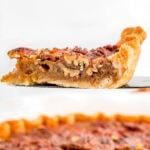 slice of pecan pie on pie server with pie beneath