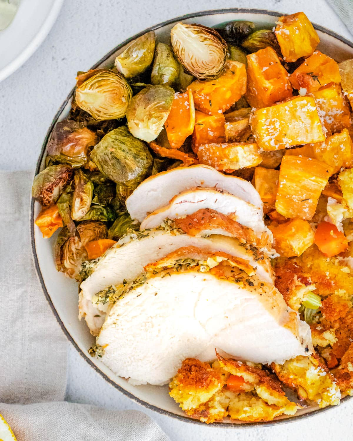 thanksgiving dinner on a plate with turkey cornbread stuffing Brussels sprouts and sweet potatoes
