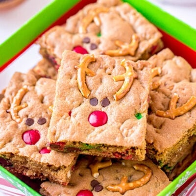 reindeer cookie bars decorated with pretzels m&ms and mini chocolate chips sitting in Christmas box