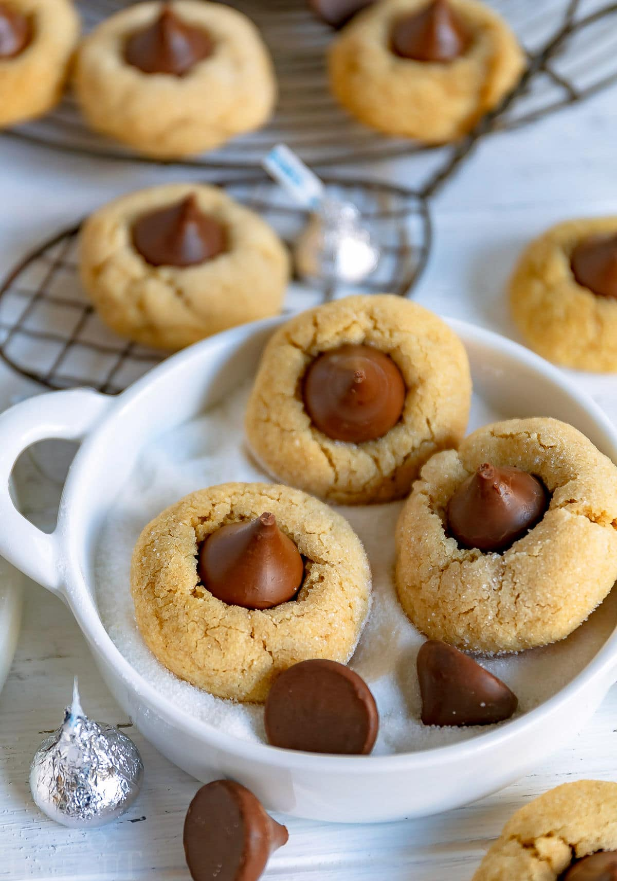 three peanut butter blossom cookies in small white bowl with sugar in it and there are more cookies in background