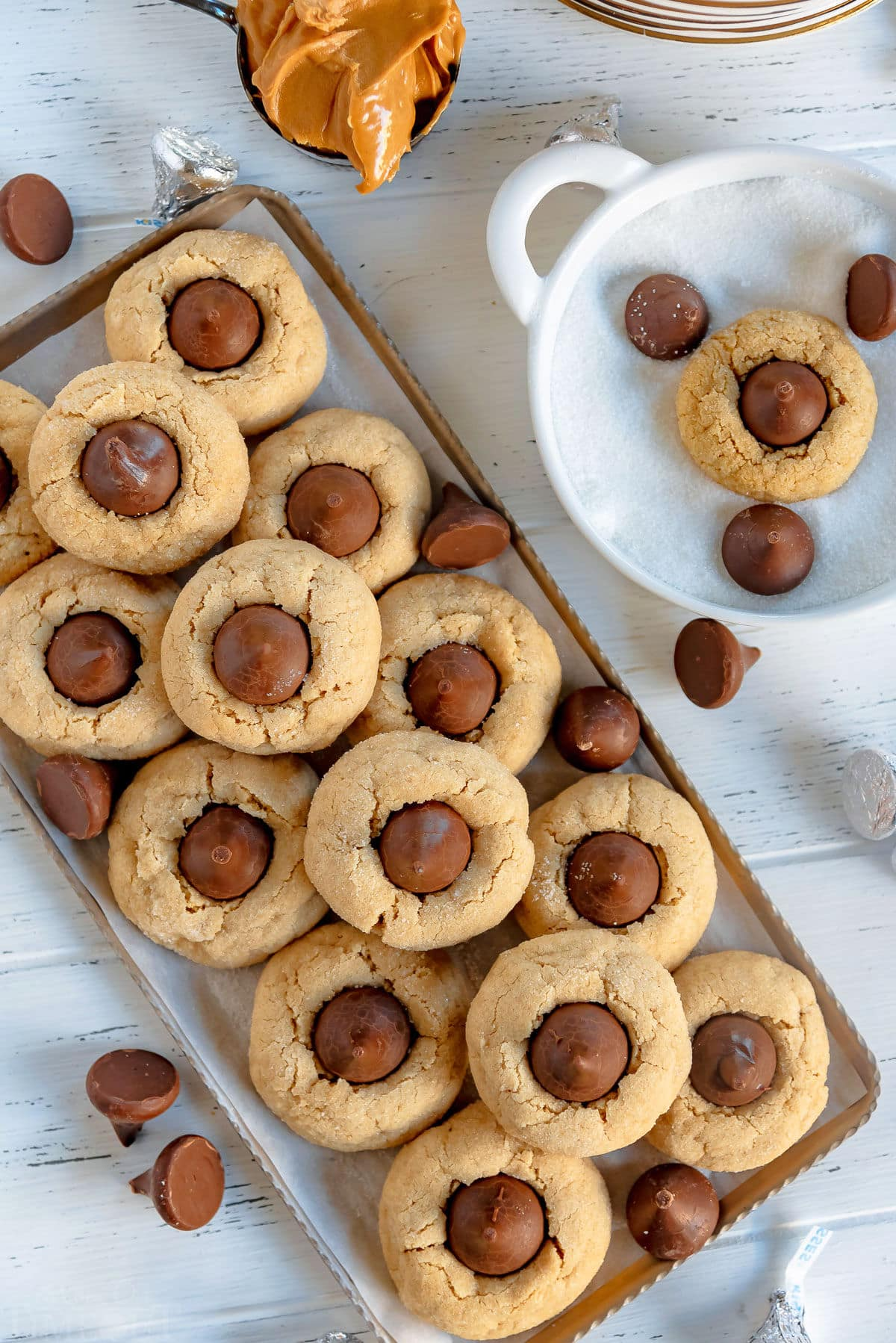top down of peanut butter blossom cookies on gray metal tray with Hershey's kisses scattered about