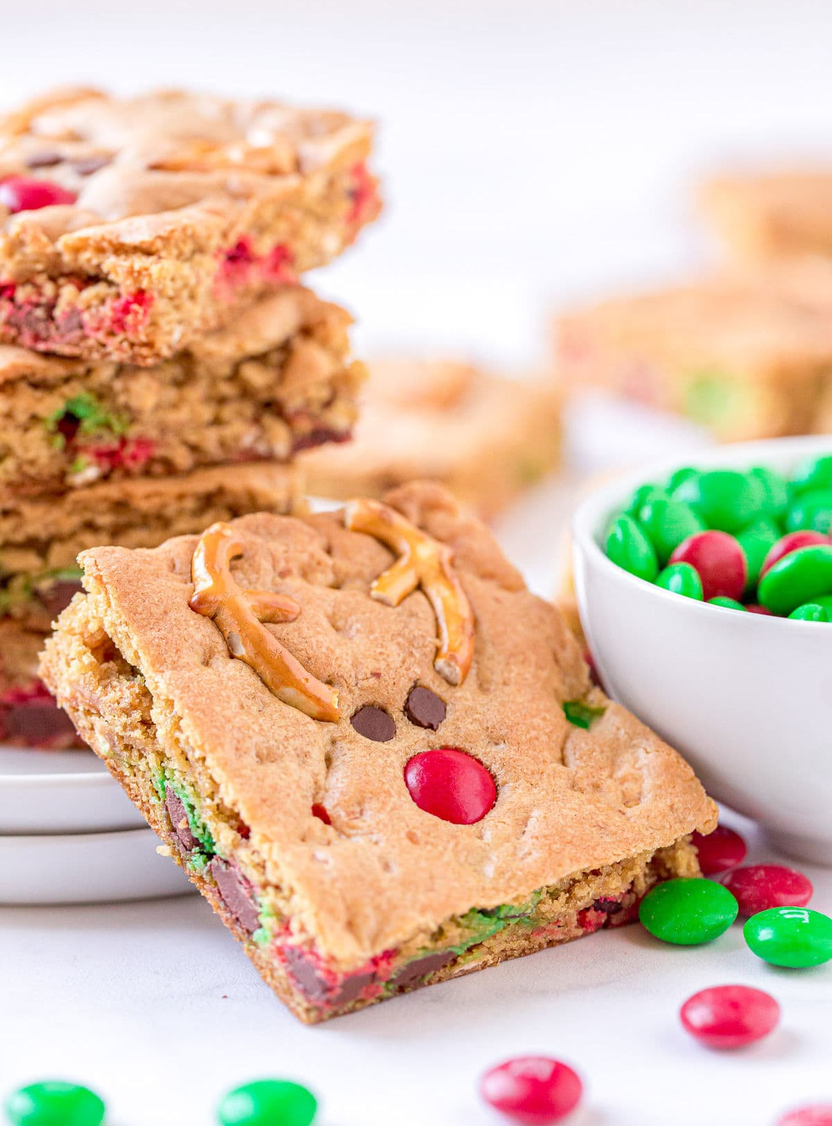 cookie bar leaned up against white plate with more cookie bars stacked on it and sitting next to a white bowl filled with red and green M&Ms