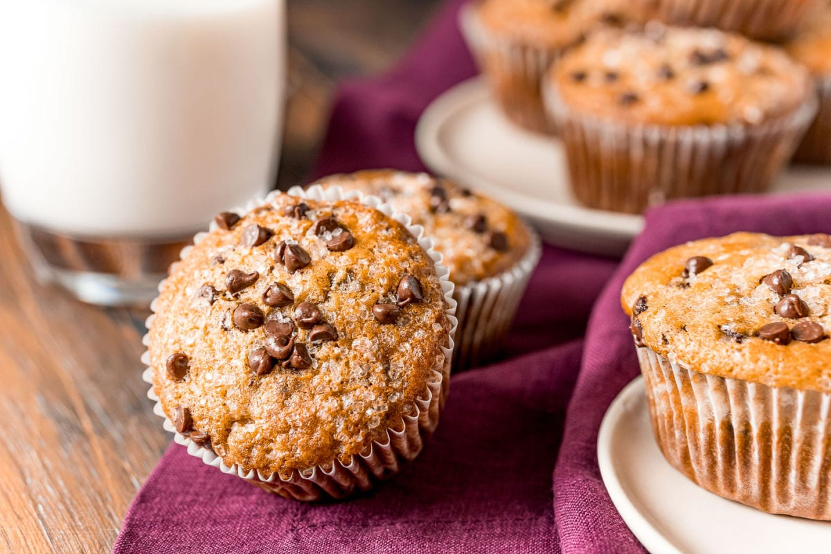 muffins scattered about on plate and burgundy napkin with glass of milk in background