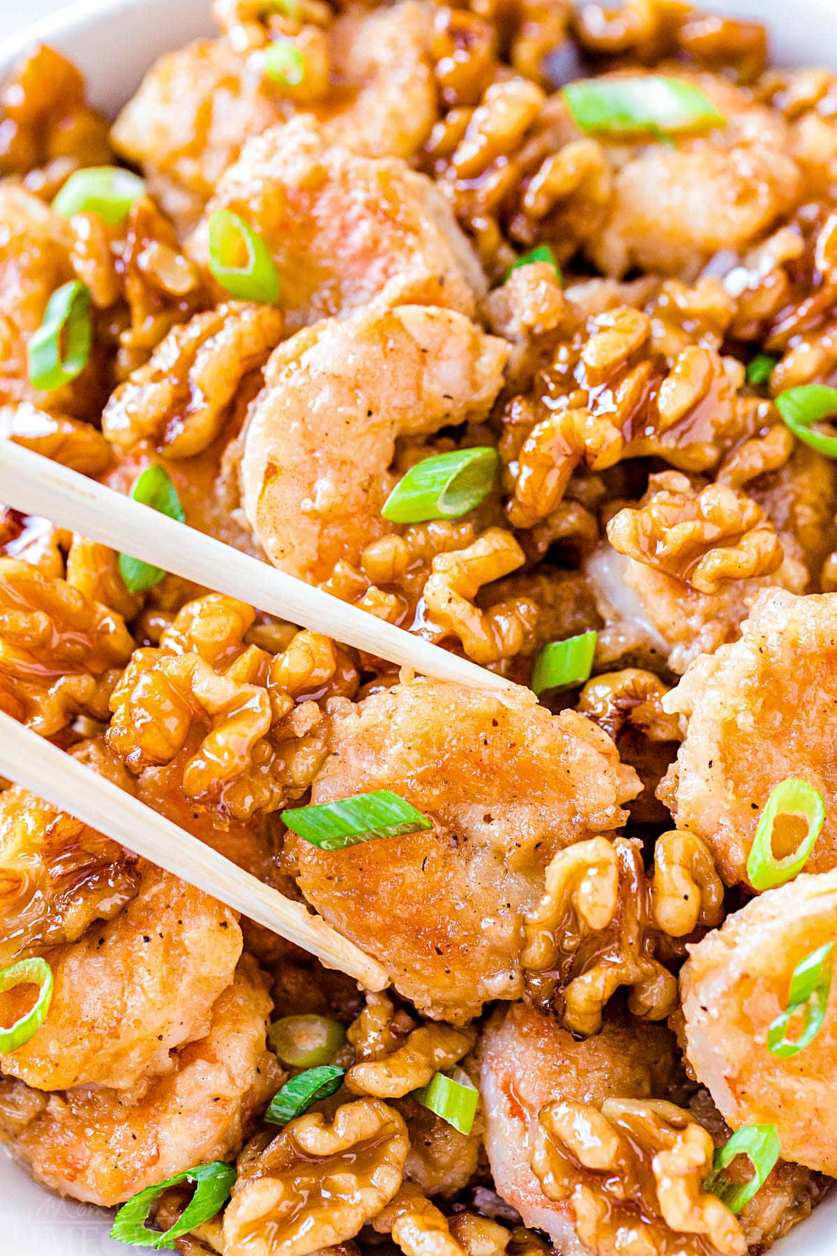 close up look at honey walnut shrimp being held with chopsticks in front of dish