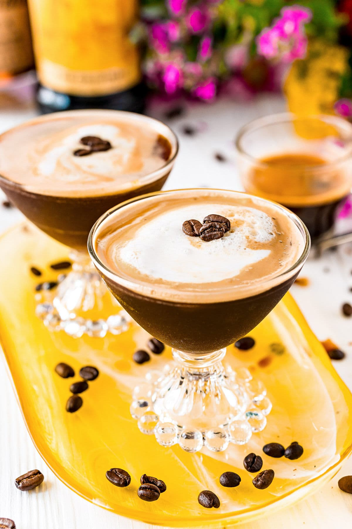 two espresso martinis on a yellow glass tray with espresso beans scattered about