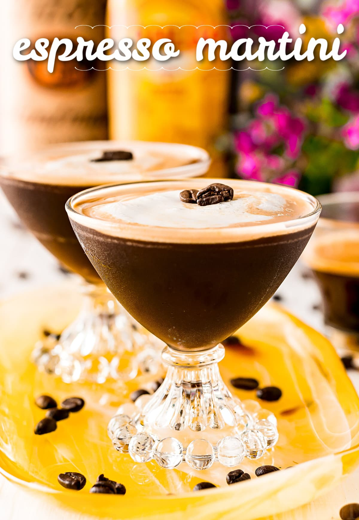 two espresso martini in fancy martini glass on yellow tray with title overlay at top of image and bottles in background
