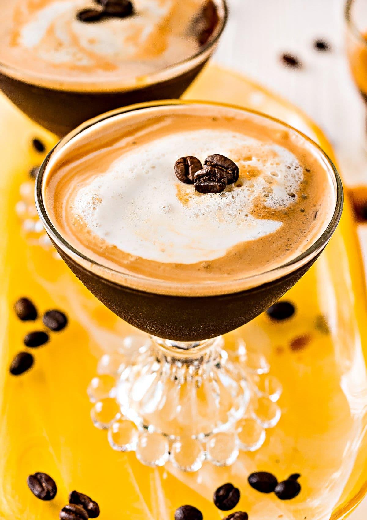 espresso martini recipe in two glasses on yellow glass tray top down view