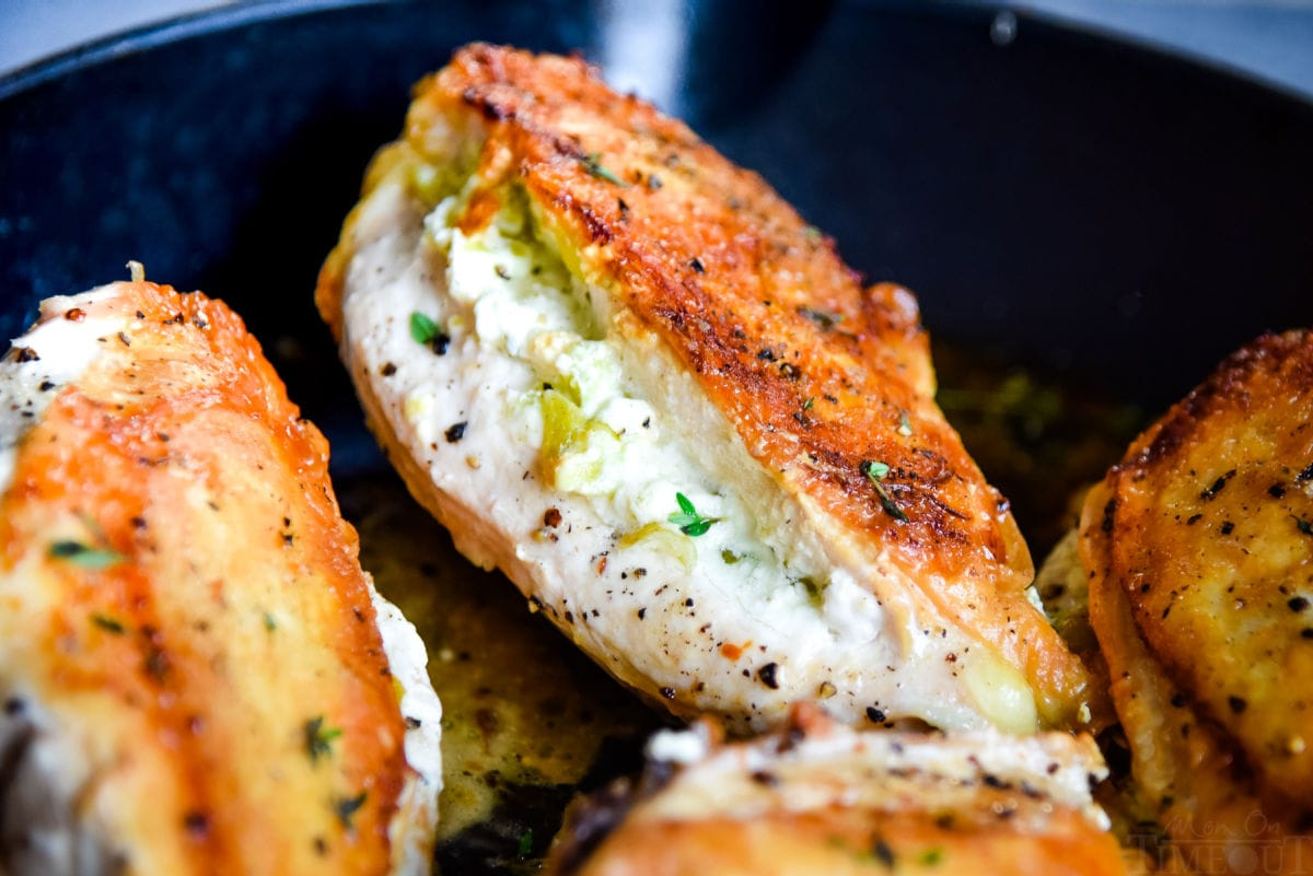 chicken breasts in skillet stuffed with pepperoncini and goat cheese with golden brown skin