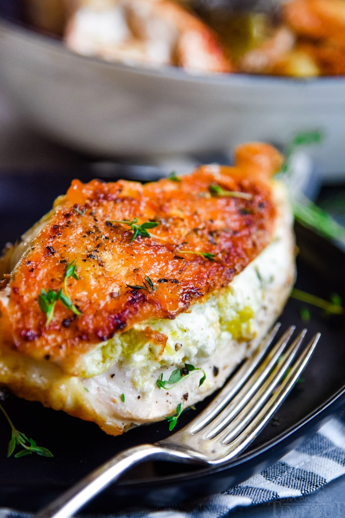 stuffed chicken with crispy skin on black plate with fork