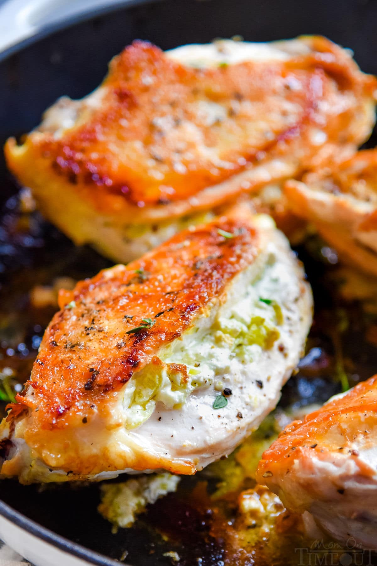 four chicken breasts in cast iron skillet stuffed with goat cheese filling