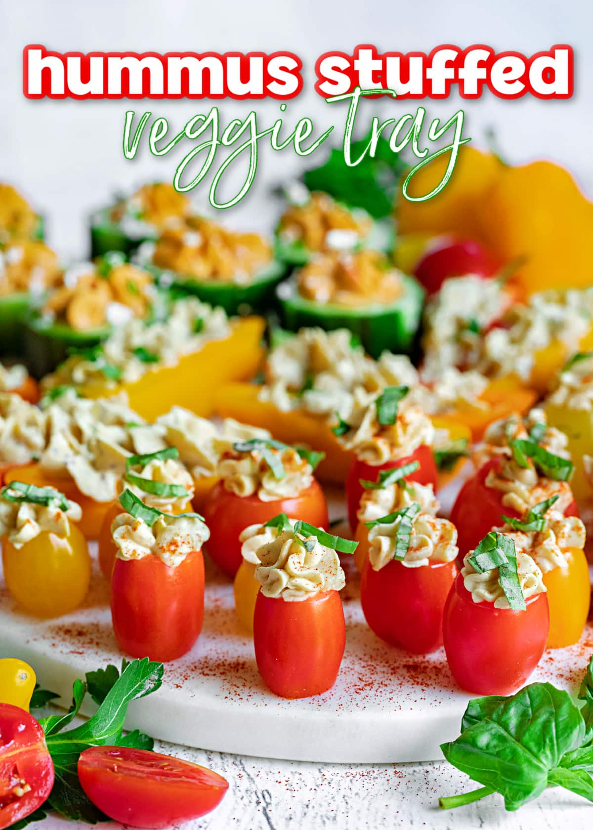 hummus stuffed veggies on white marble tray topped with herbs and title overlay at top
