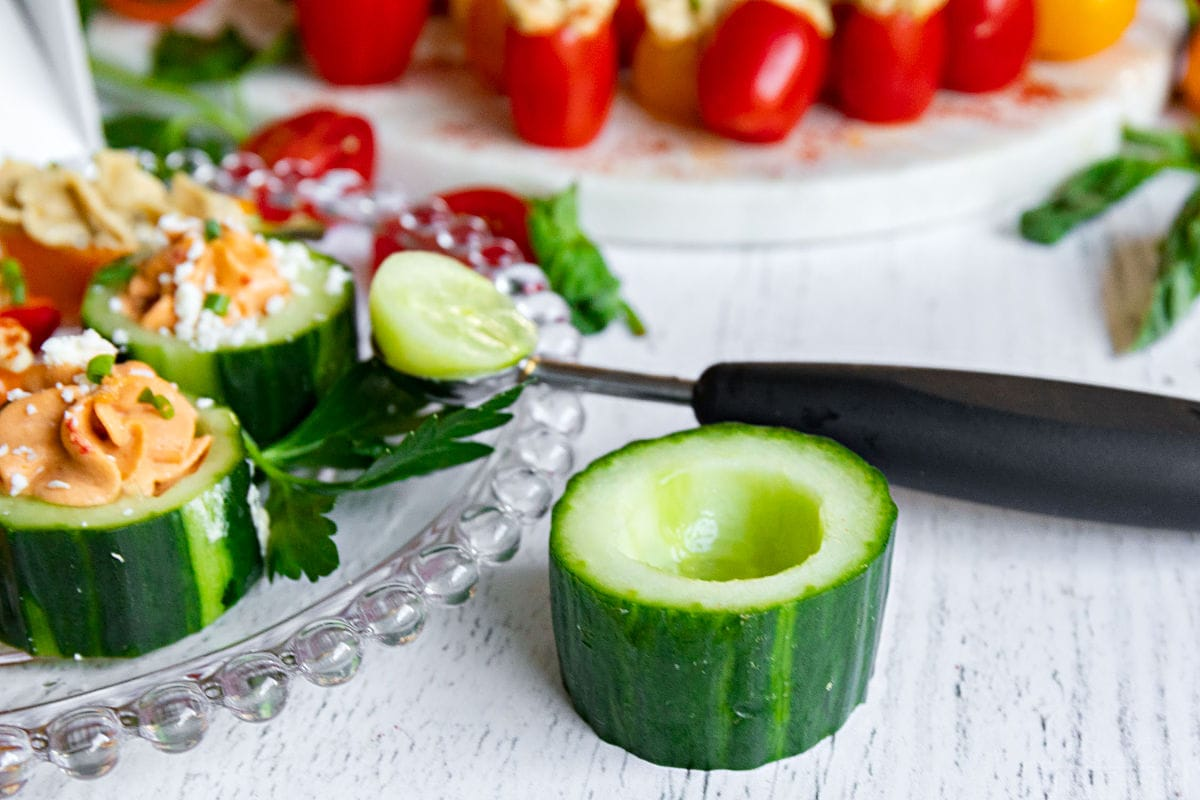 cucumber cup with melon baller next to a plate of hummus stuffed veggies
