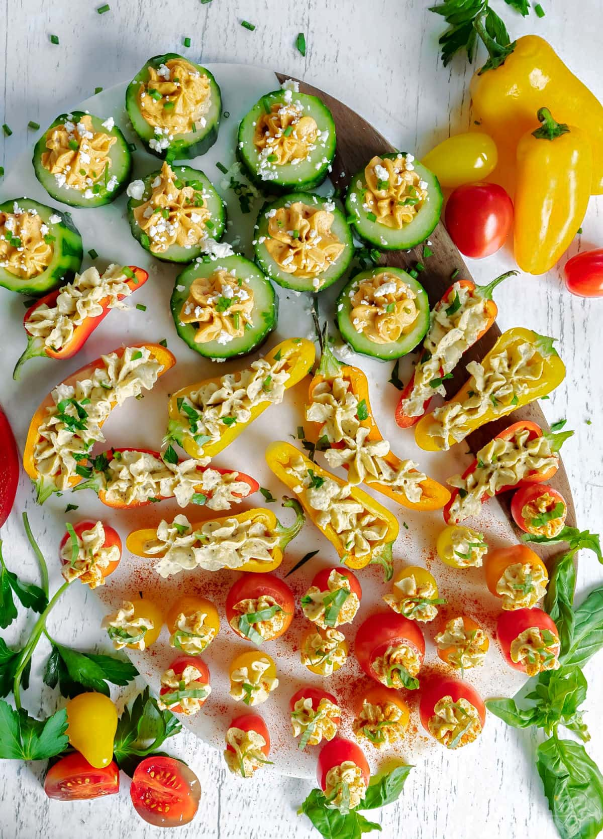 top down look at veggies stuffed with hummus and topped with herbs