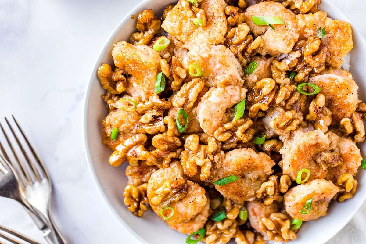 top down view of honey walnut shrimp in white bowl with forks near it on the left side and the dish is garnished with green onion