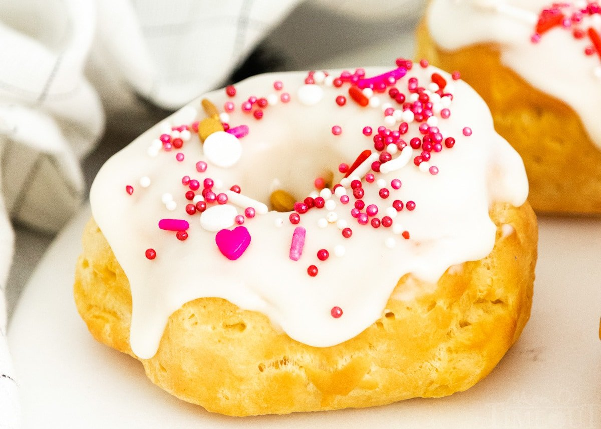 air fryer biscuit donut topped with vanilla glaze and sprinkles