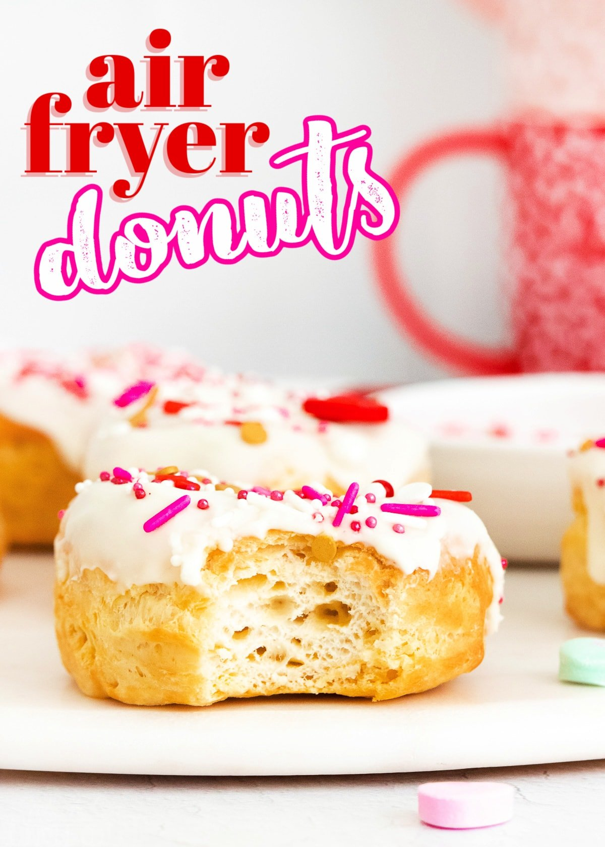 air fryer donut with vanilla glaze and valentines day sprinkles with bite taken and title overlay at top of image