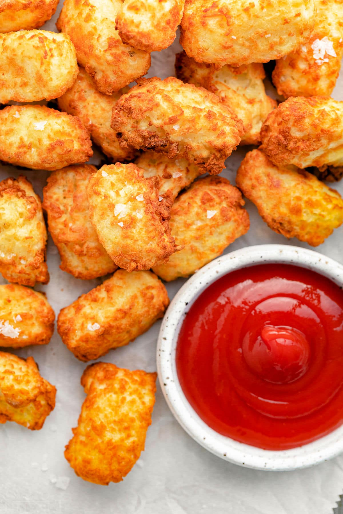close up of golden crispy tater tots with ketchup.