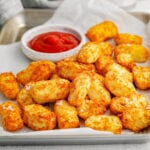 tater tots ready to be eaten with ketchup.