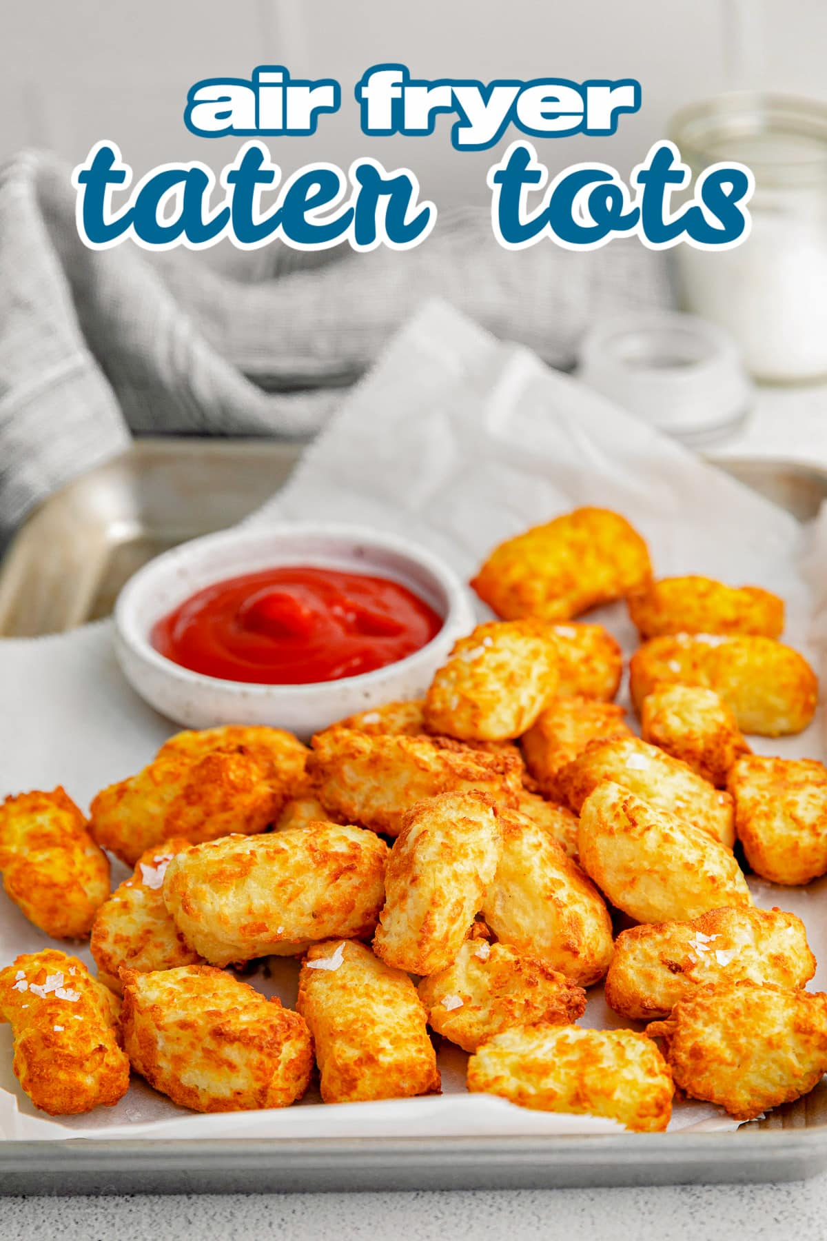 tater tots on sheet pan with small bowl of ketchup and title overlay at top of image.
