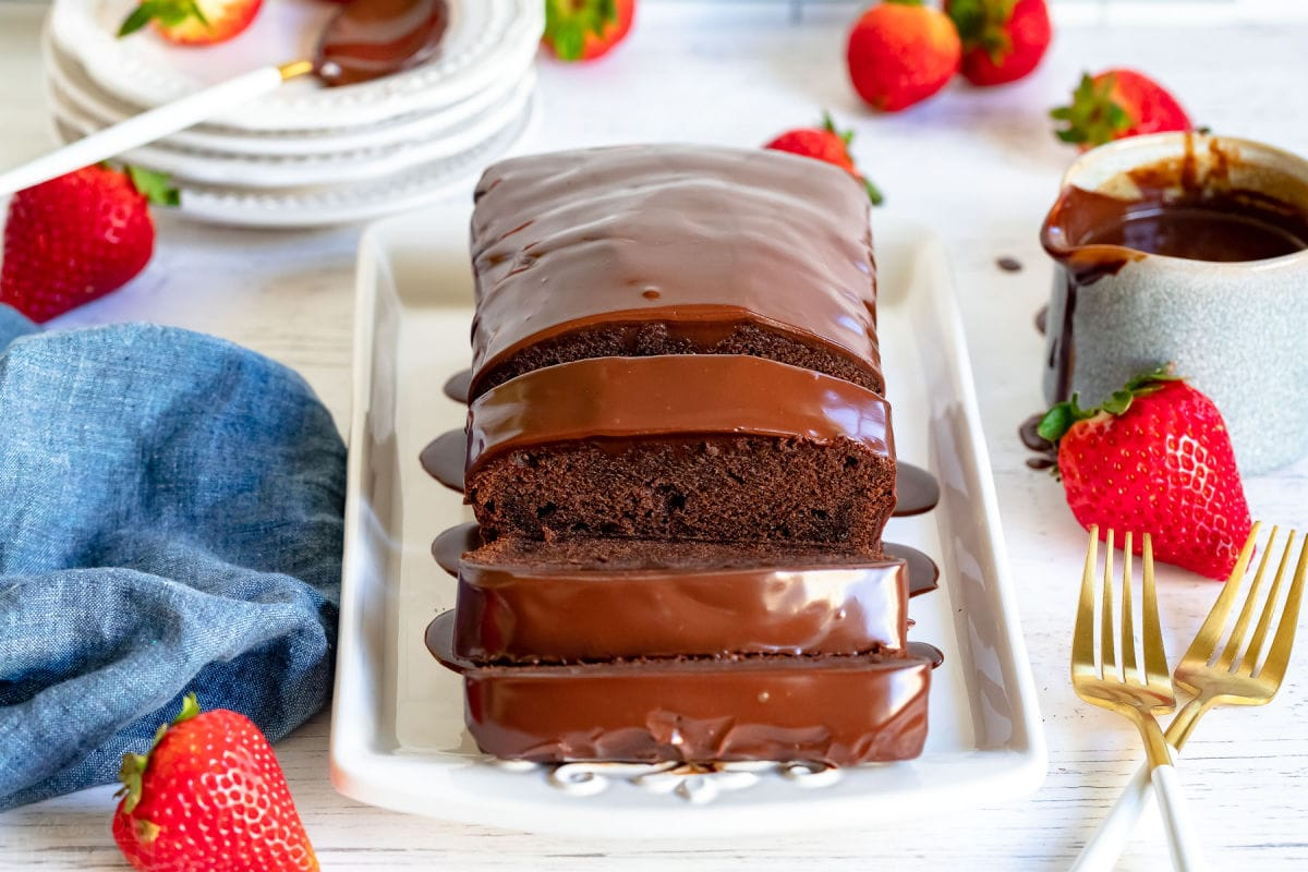 chocolate pound cake loaf with three slices cut on white tray with gold forks next to it and strawberries scattered about