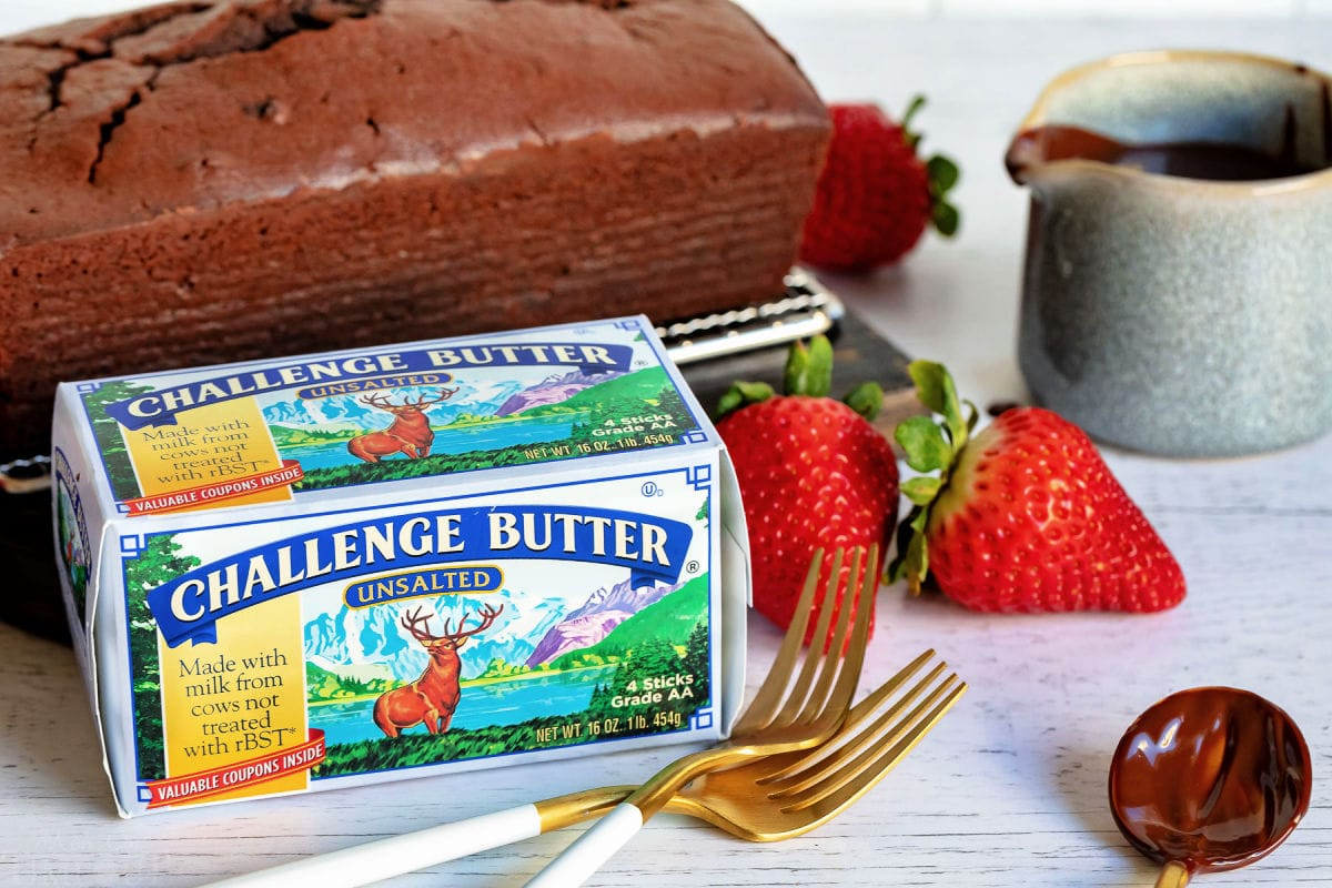 chocolate pound cake with challenge butter box sitting in front with a couple forks and strawberries