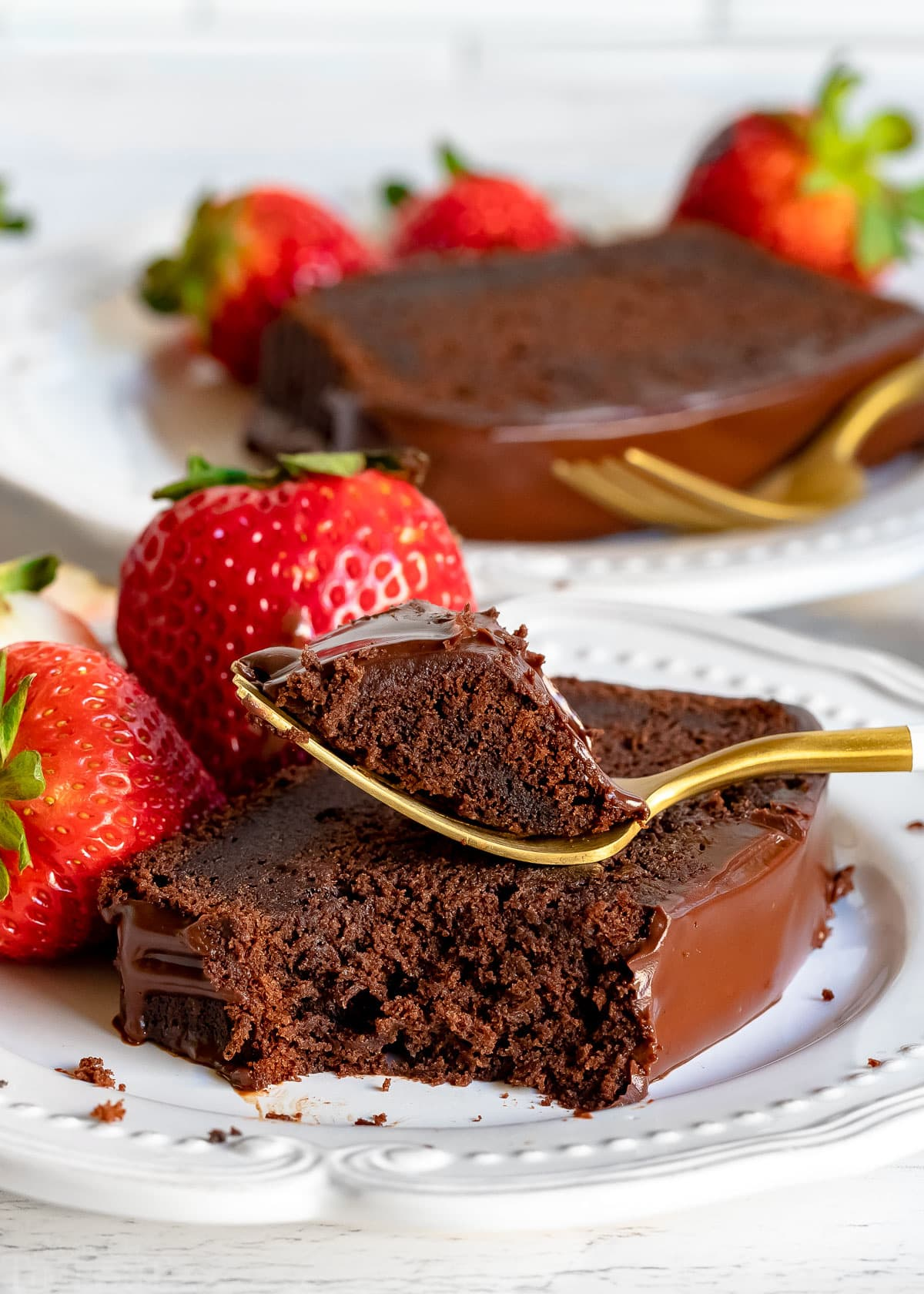 piece of chocolate pound cake with a forkful taken on a white plate with another piece in background served with strawberries
