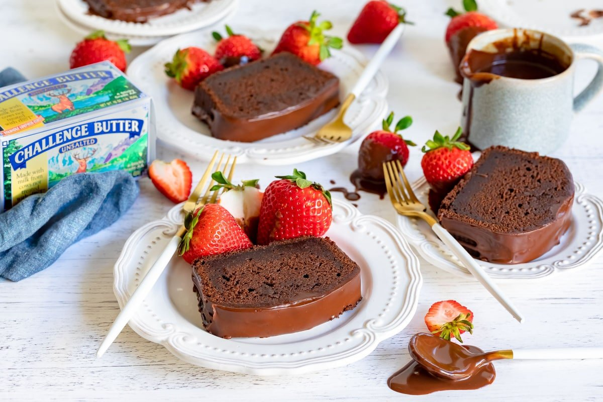 chocolate pound cake sliced and served on plates with chocolate glaze and strawberries
