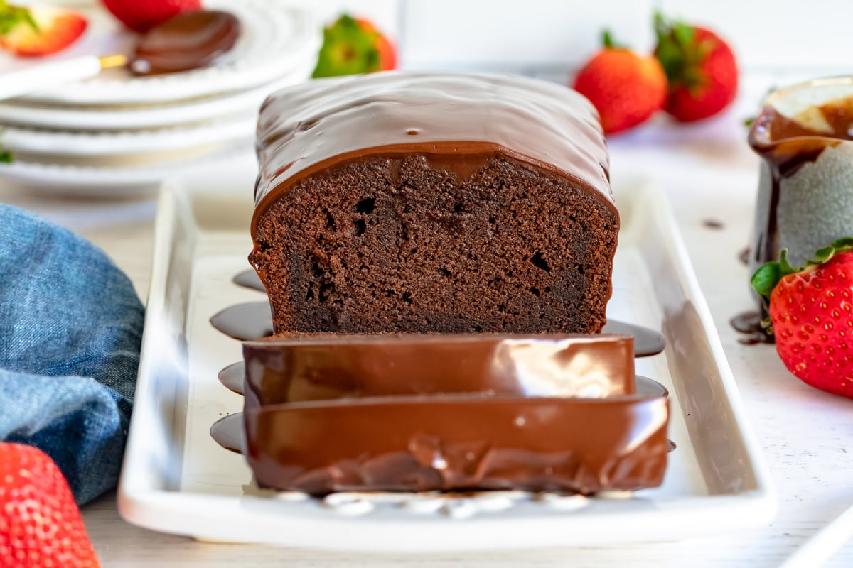 chocolate pound cake loaf with three slices cut on white platter with gold forks next to it and strawberries scattered about and blue napkin to the left
