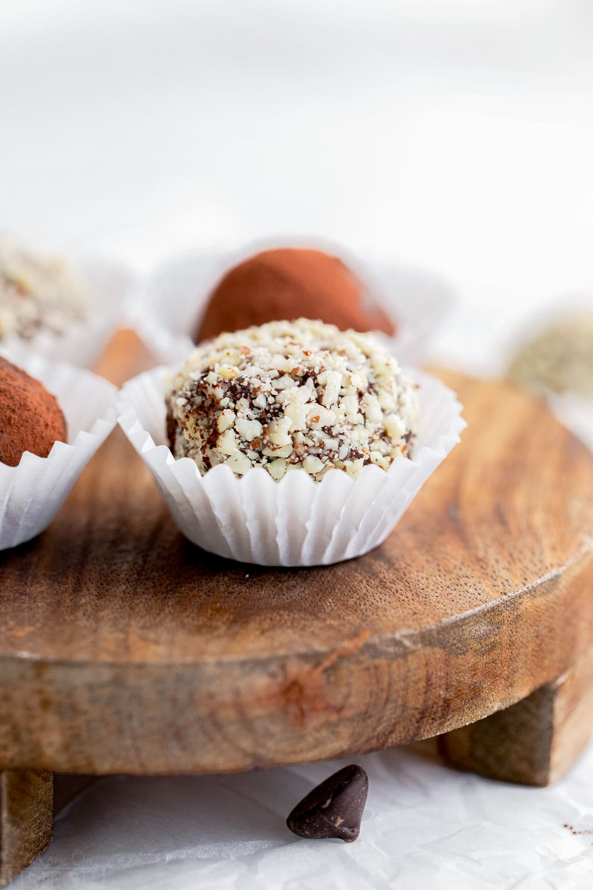 chocolate truffle coated in almonds in white paper cup on wood board
