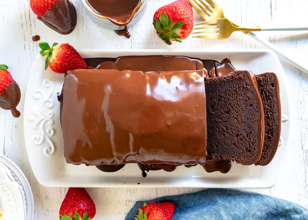 chocolate pound cake with chocolate ganache glaze on white tray with two slices cut
