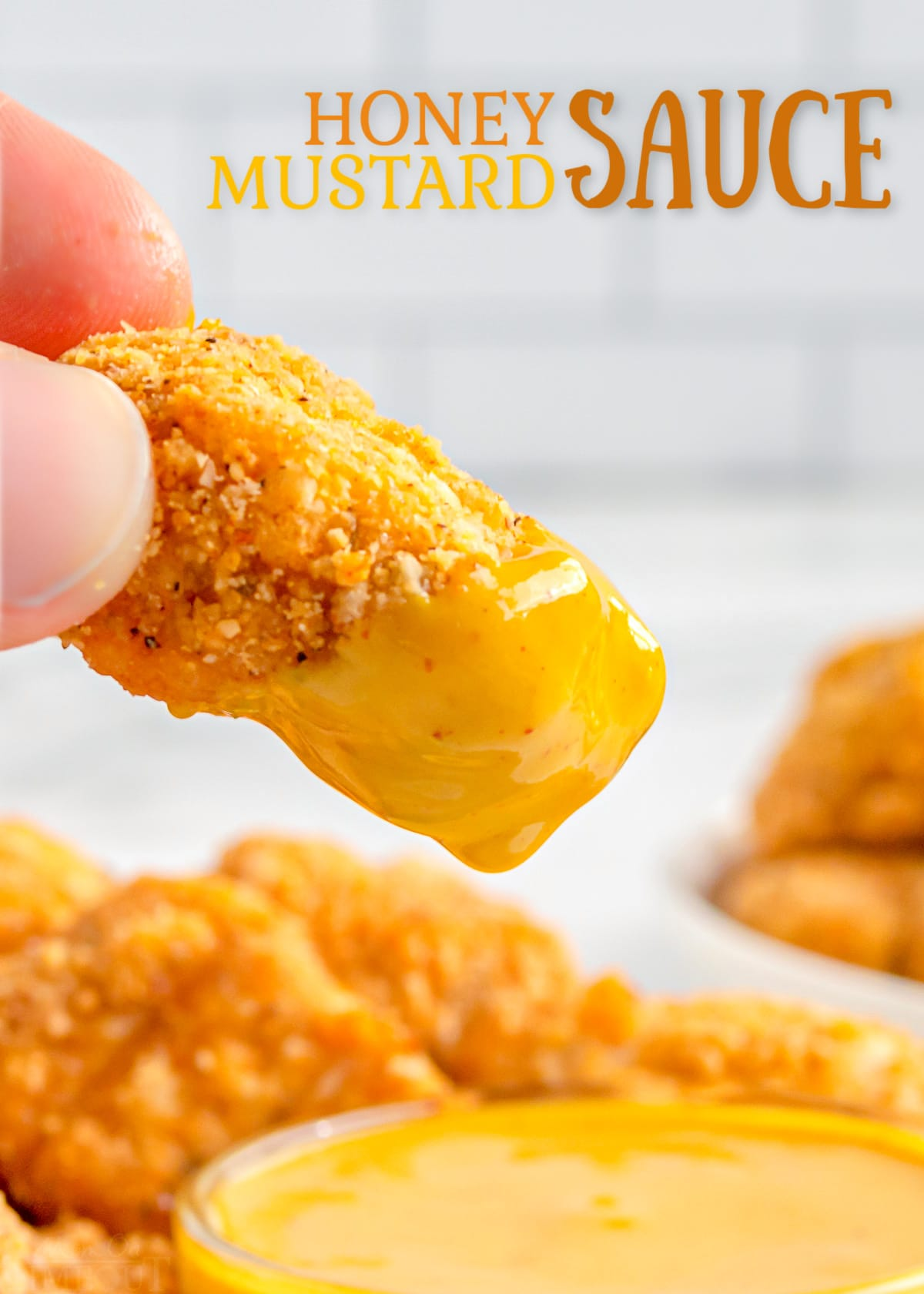 chicken nugget being dipped in honey mustard.