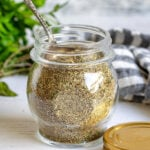 italian seasoning in a small glass jar with a spoon in the jar.