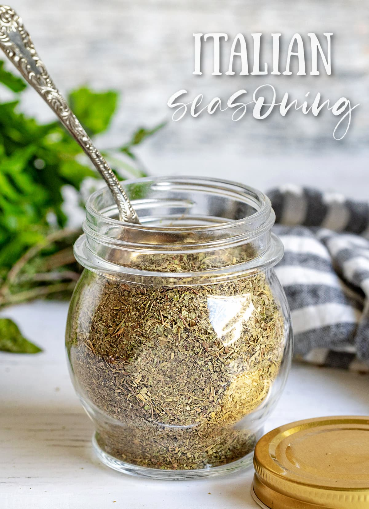 italian seasoning in a small glass jar with a spoon in the jar and title at top of image.