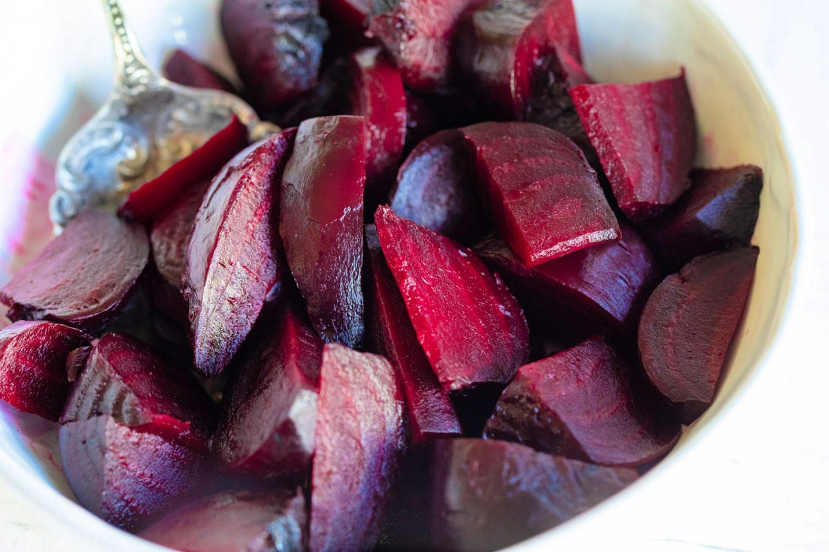 beets that have been roasted and cut into small pieces in a large white bowl.
