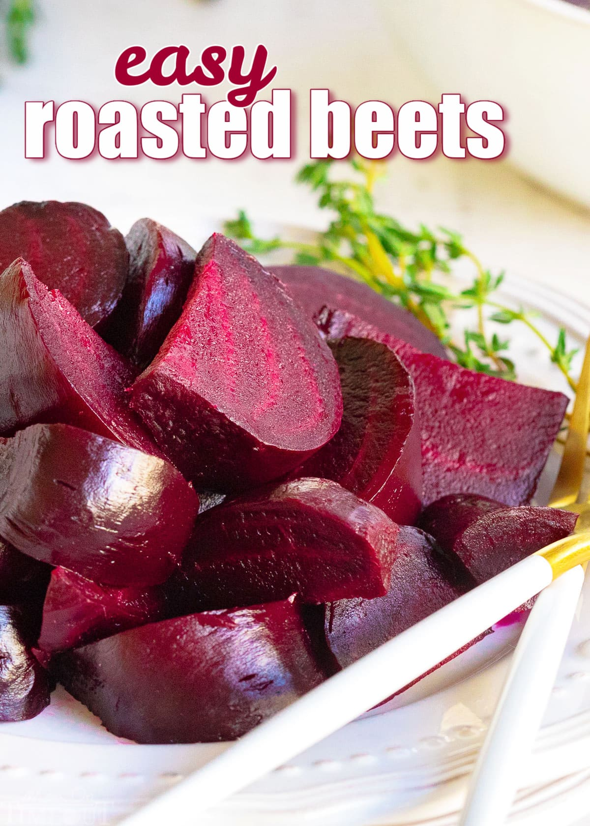 roasted beets cut into wedges on white plate with thyme sprig on plate.