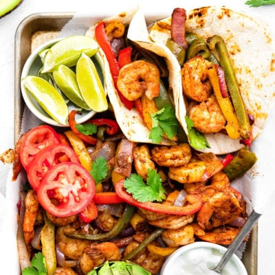shrimp fajitas on a sheet pan with all the fixings including avocado lime wedges tomatoes and sour cream.