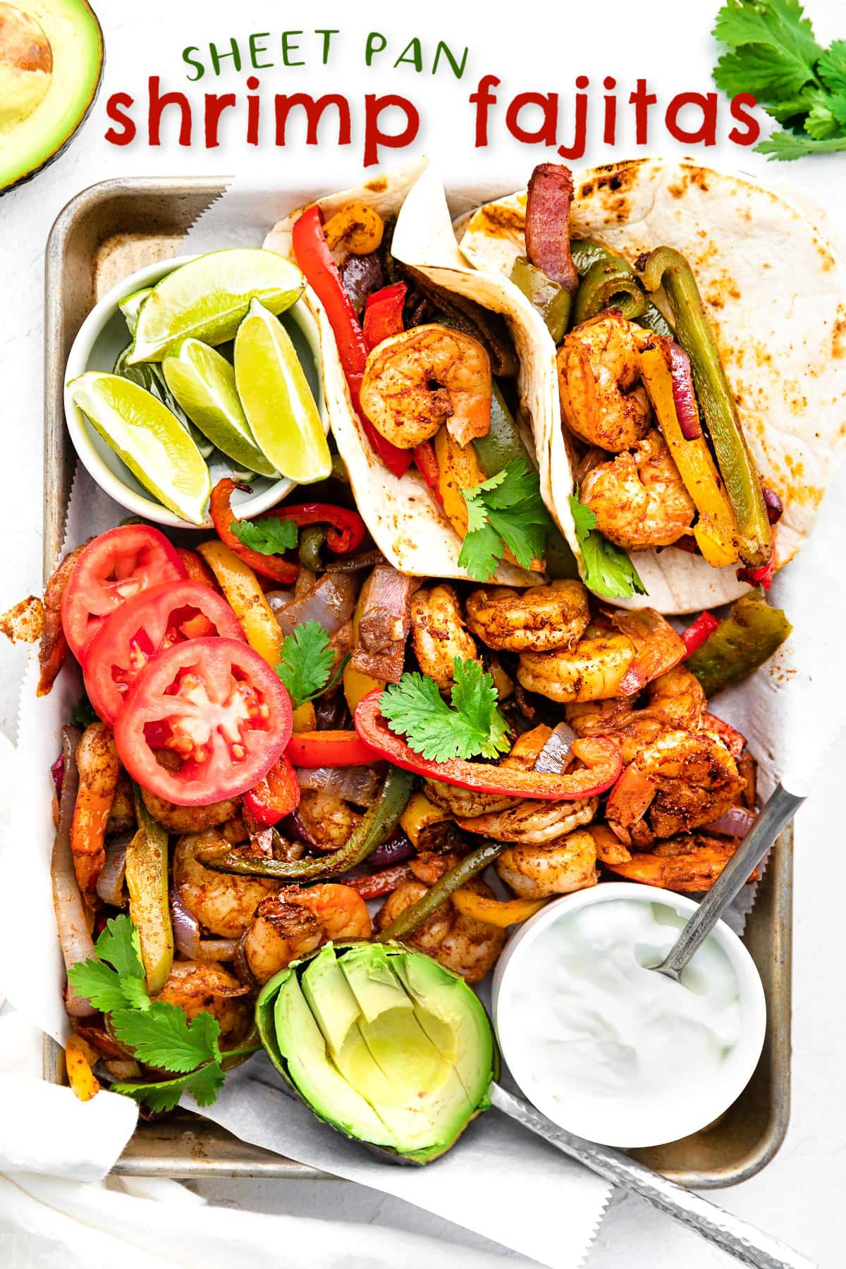 shrimp fajitas on a sheet pan with all the fixings including avocado lime wedges and sour cream.